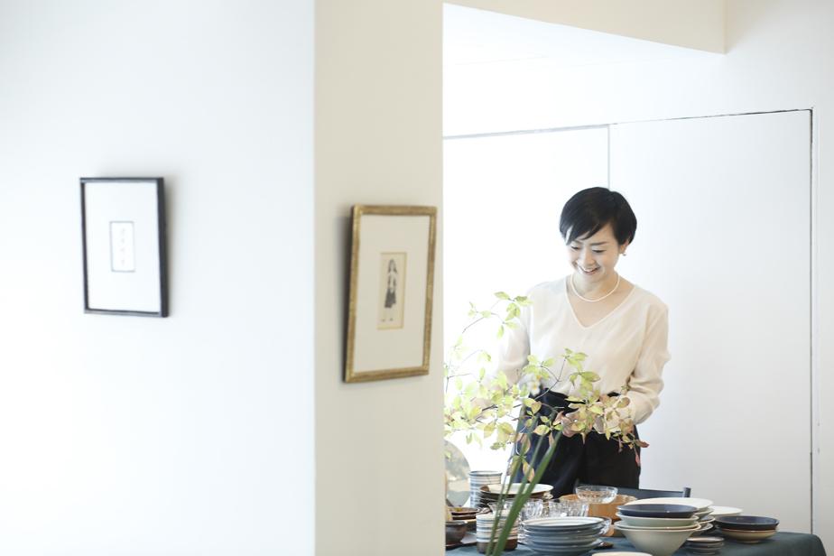 テーブル周りをコーディネートする永松さん。隣り合う器の組み合わせや植物染めのテーブルクロスの色はよく吟味され、店内の所々に新鮮な花が生けられる。