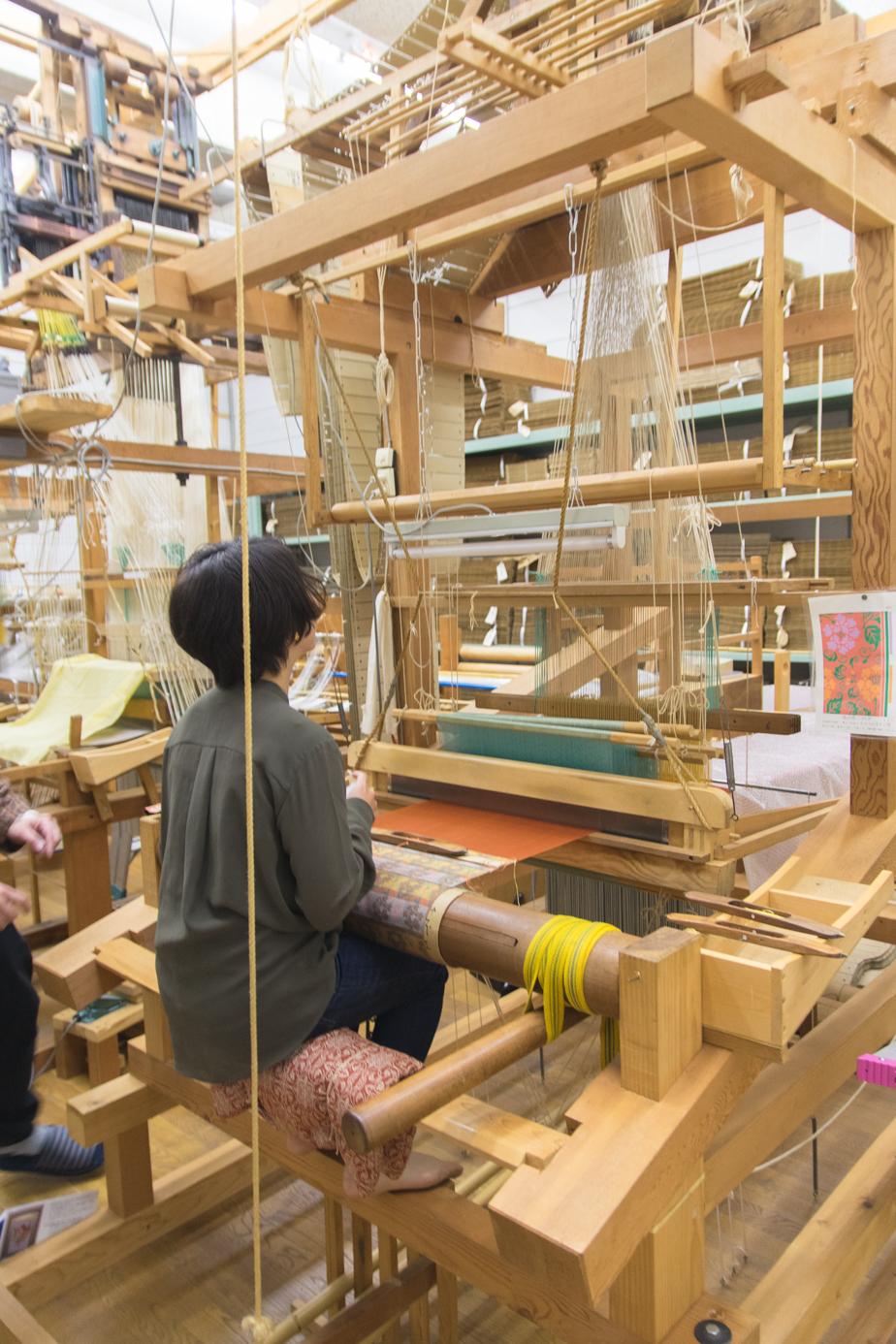 「高機」と呼ばれる難易度の高い手織り機。とても大きく、身長150cm未満の私は、足を踏木に伸ばすので精一杯!