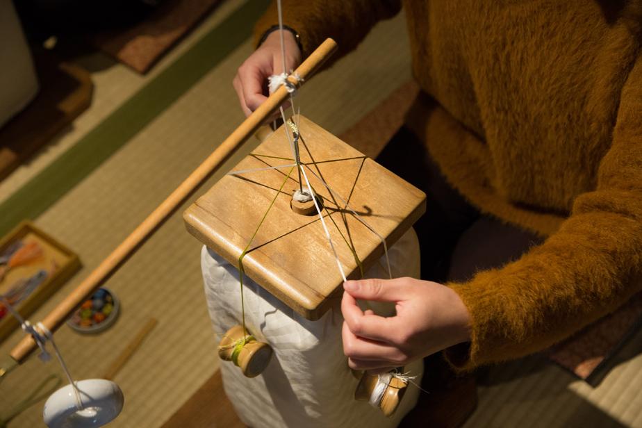 糸の束を持ち上げると思っていたより重たくてびっくり!重りは糸巻きの機能も兼ねています。