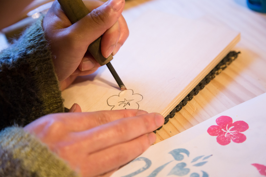 トレーシングペーパーとカーボン紙を使って反転させた図案を版木に写し、版木刀で線に切り込みを入れます。