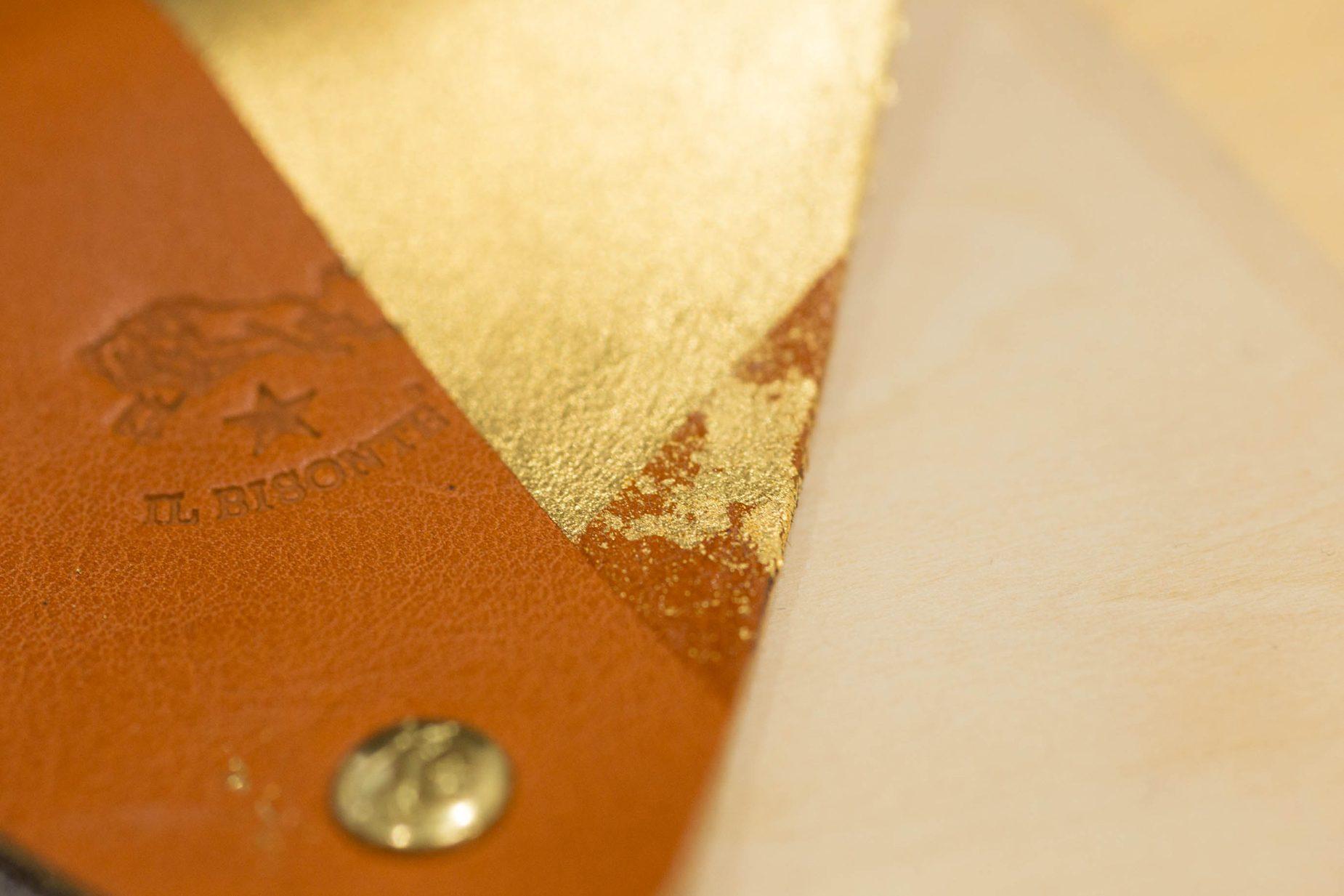 完成した革のコインケース。刷毛で余計な金箔を払った時、失敗して押せなかった部分に細かい金箔が付着し、模様のようになりました。