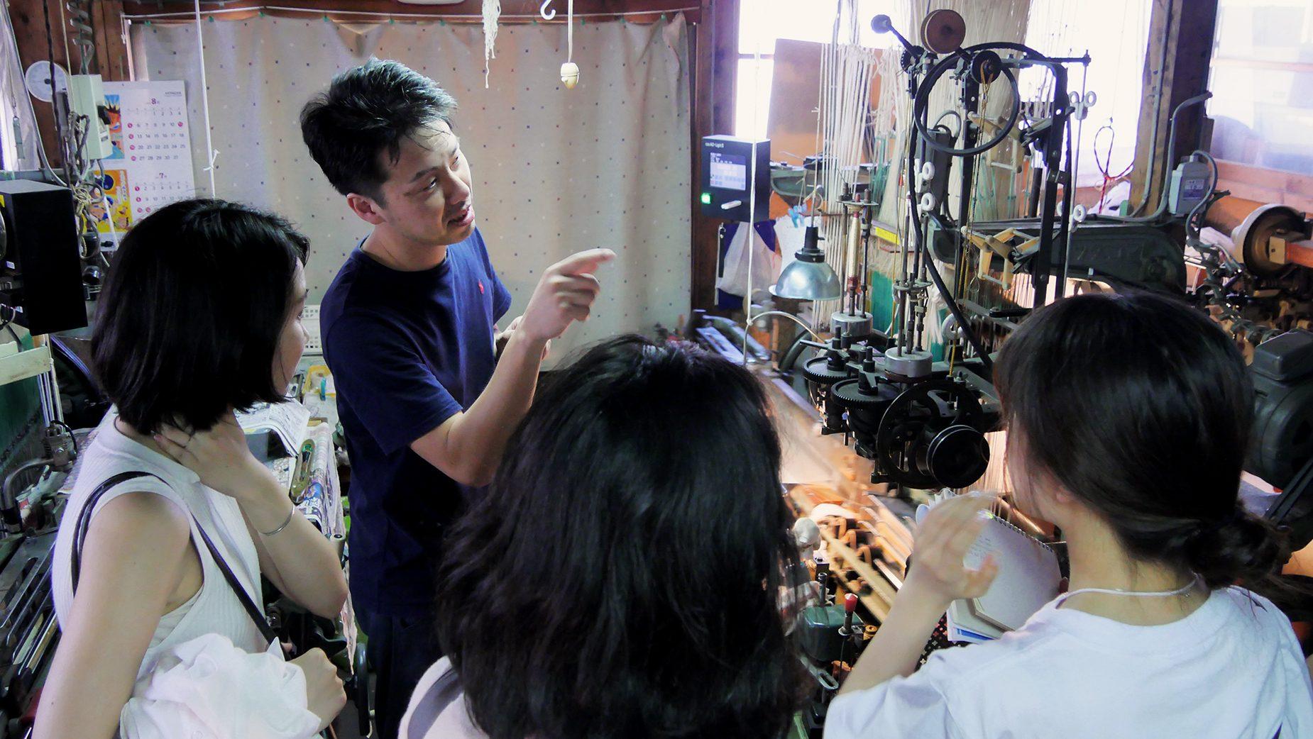 工房の中で参加者たちに丁寧に織りの工程や紋織物について説明する羽賀さん。