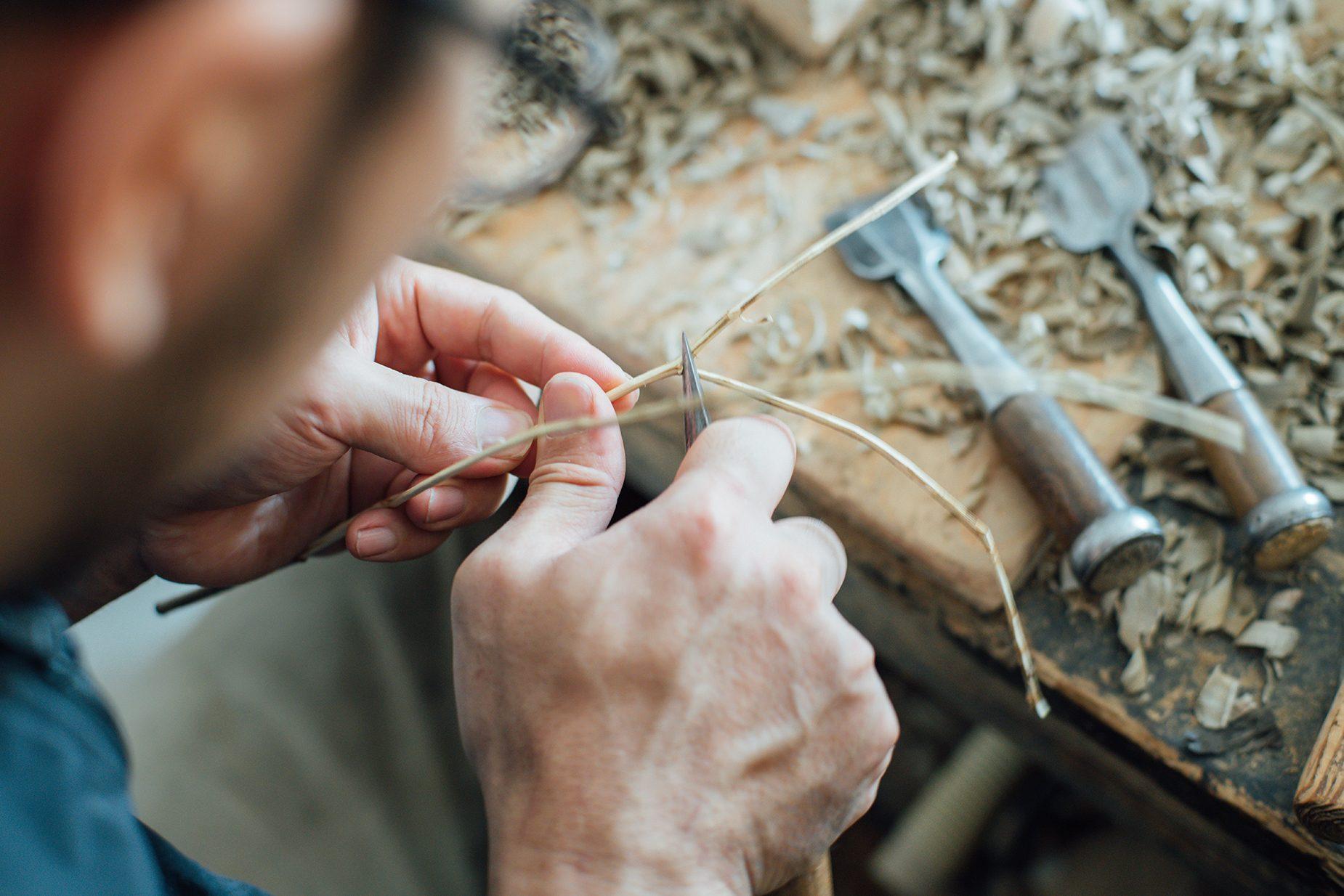 仕上げの作業は細やか。手斧を振り下ろす体の大きな動きとは相反する。最近はより繊細な枝を使った作品も。