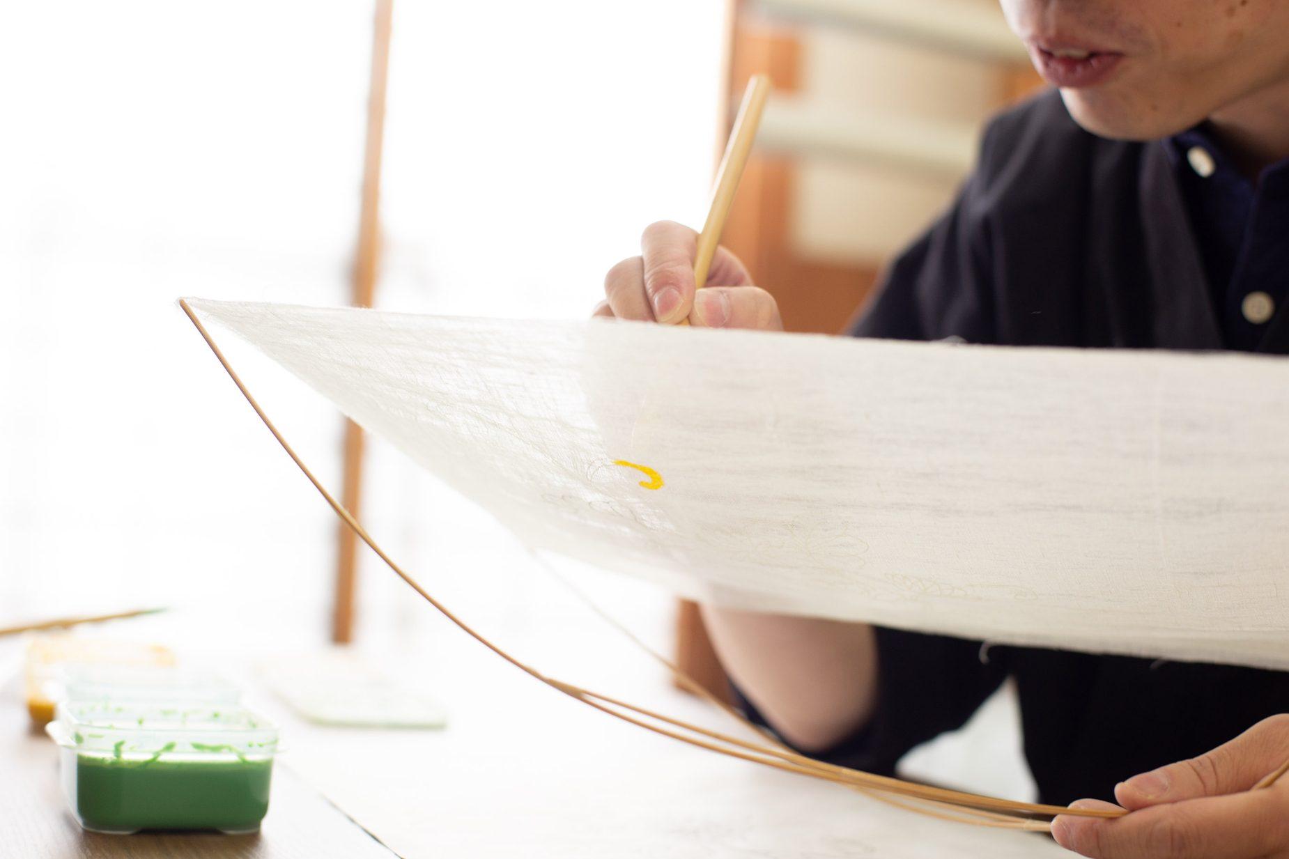 先端に針がついた竹の棒を生地の四つ角に挿し、ピンと張ります。さらに、片手で竹のクロスする部分を固定します。